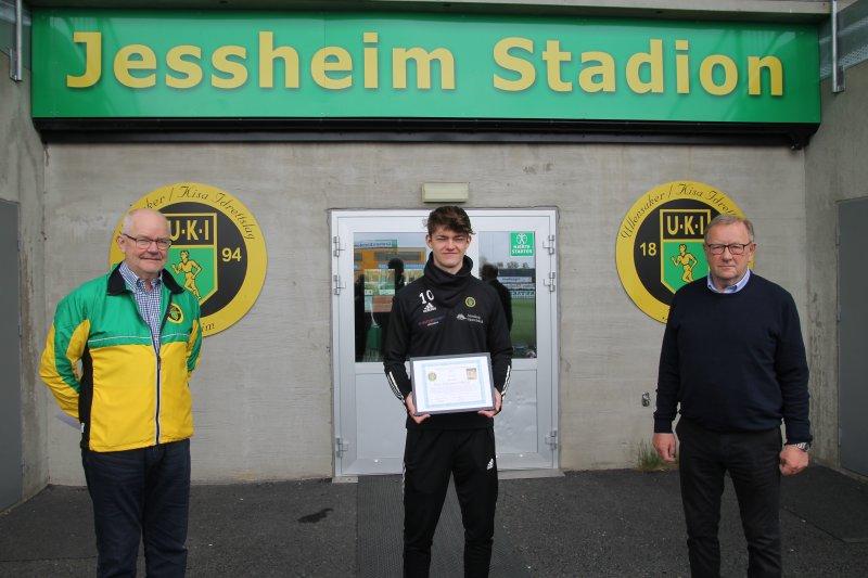 Ole Kristian Wiig (t.v.) og Trond-Ivar Johansen (t.h) delte ut Oddvar Jensens Idrettspris for 2021 til Elias Sebastian Solberg torsdag.